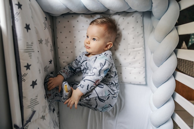 Top view of cute playful blond little baby boy lying in his crib in the morning and playing with his feet.