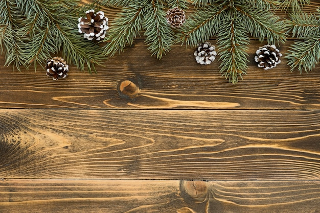 Top view cute winter pine needles on wooden background