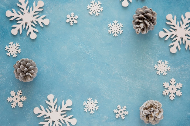 Top view cute winter snowflakes and pine cones