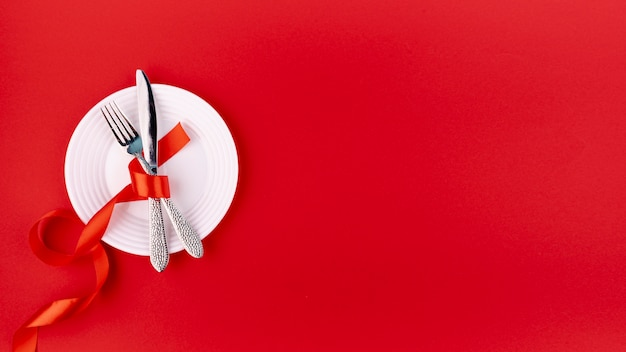 Top view of cutlery on plate with ribbon and copy space