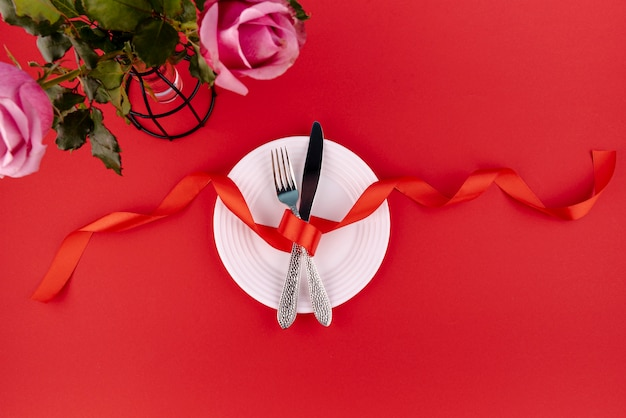 Top view of cutlery on plate with ribbon and roses
