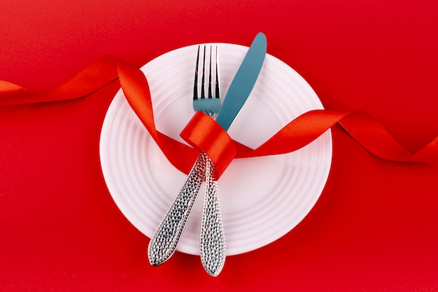Top view of cutlery on plate with ribbon