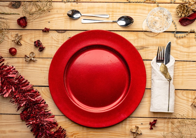 Top view of cutlery and plates on festive wooden background