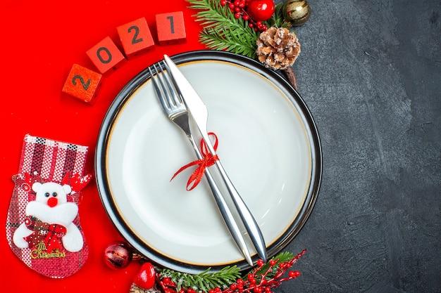 Vista dall'alto del set di posate sul piatto della cena accessori decorativi rami di abete e numeri calza di natale su un tovagliolo rosso su sfondo nero