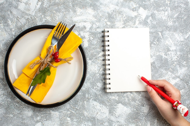 Top view of cutlery set for meal on a white plate and hand writing on closed notebook on ice surface