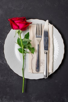 Top view cutlery with a rose on a plate
