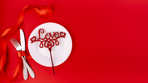 Top view of cutlery with valentines day ornament and copy space