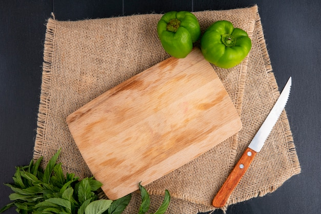 Top view of cutting board with bell pepper knife and mint on a beige napkin