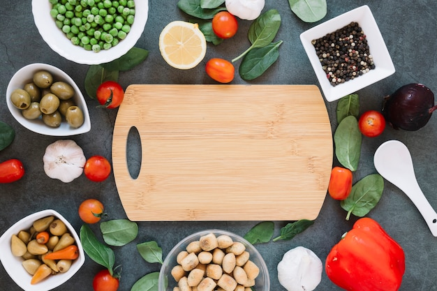 Top view of cutting board with cherry tomatoes and spinach