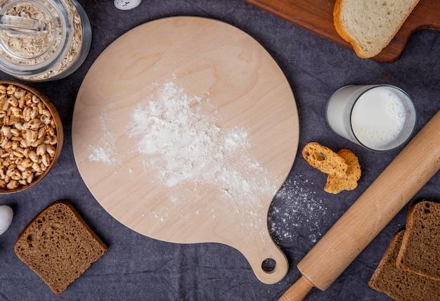 Vista superiore del tagliere con il mattarello dei fiocchi di avena-fiocchi del latte e della farina intorno su fondo marrone rossiccio
