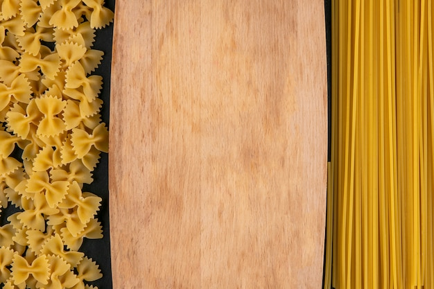 Top view of cutting board with raw pasta and spaghetti on a black surface