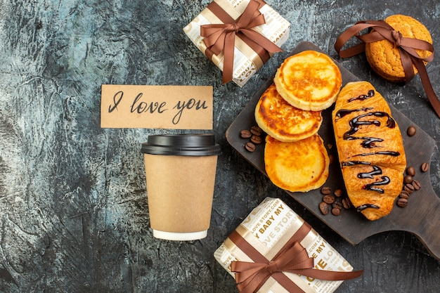 Top view of cutting board with tasty breakfast with pancakes croisasant stacked cookies beautiful gift boxes coffee on dark surface
