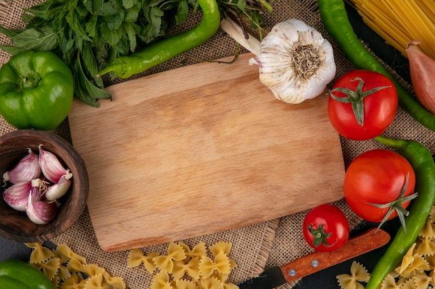 Top view of cutting board with tomatoes garlic bell and hot peppers and onions with mint on a beige napkin