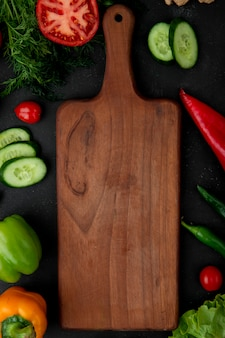 Top view of cutting board with vegetables as fennel tomato cucumber pepper around on black background