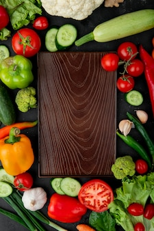 Top view of cutting board with vegetables as pepper tomato zucchini garlic and others around on black background