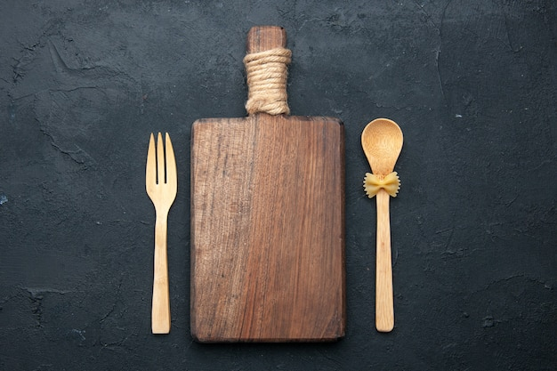 Top view cutting board wooden spoon and fork on dark surface