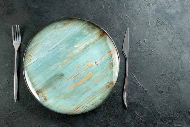 Вид сверху голубая круглая тарелка, вилка и нож на темной поверхности