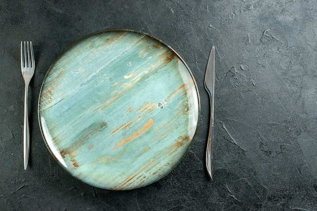 Top view cyan round plate fork and knife on dark surface copy place