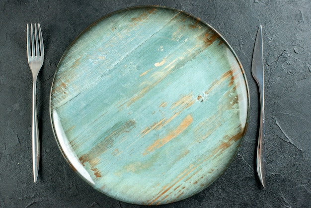 Top view cyan round plate fork and knife on dark surface