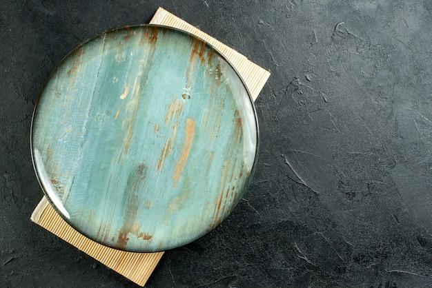 空き領域のある黒いテーブルにシアンの丸いプラッターベージュボードの上面図