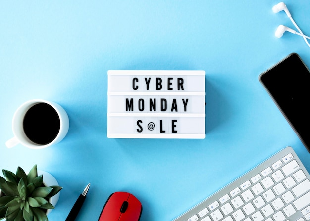 Top view of cyber monday light box with smartphone and coffee
