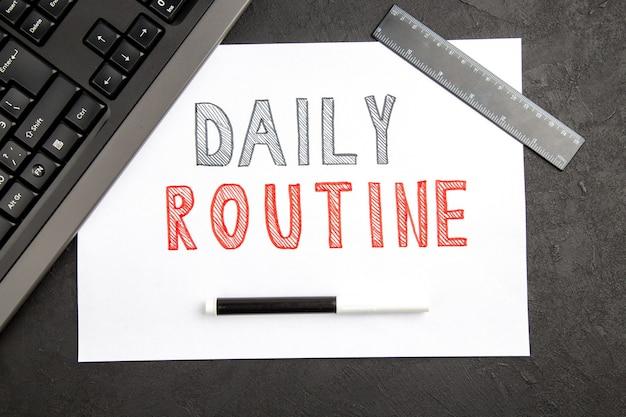 Vista dall'alto scrittura di routine quotidiana su uno spazio vuoto su una foto del blocco note del quaderno a colori della superficie scura