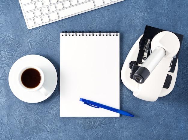 Top view of dark blue desktop  microscope, notepad, computer. , empty ,