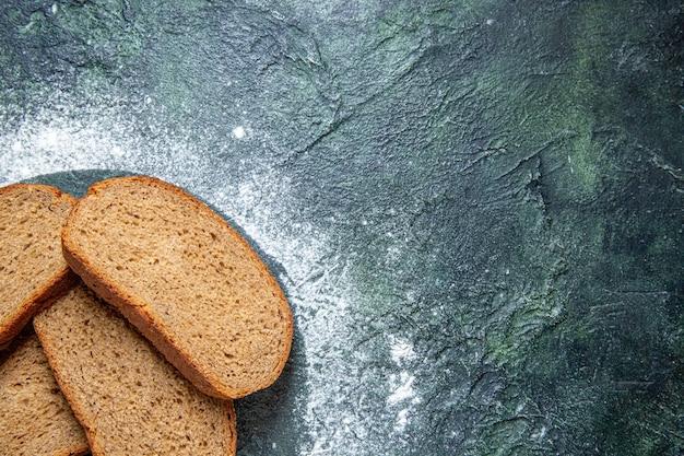暗い机の上のトップビューの暗いパンのパン 無料写真