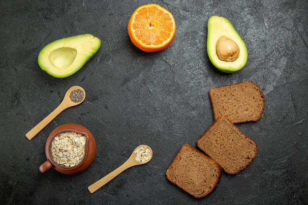Top view of dark bread loafs with avocados on grey surface