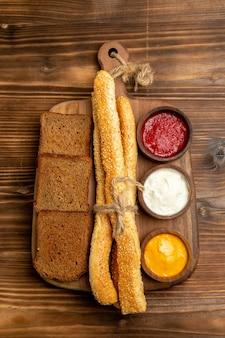 茶色の机の上にパンと調味料が入ったトップビューのダークパンパンスパイシーなフードパンパン