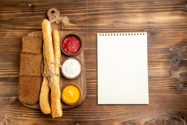 갈색 책상 음식 빵 롤빵 매운 빵 메모장과 조미료와 상위 뷰 어두운 빵 덩어리