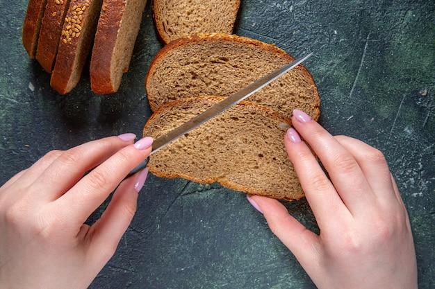 Pagnotte di pane scuro vista dall'alto con taglio femminile sulla scrivania scura