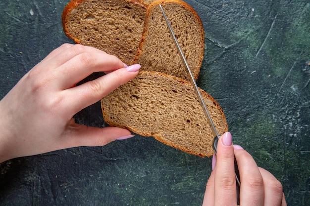어두운 책상에 여성 절단과 상위 뷰 어두운 빵 loafs