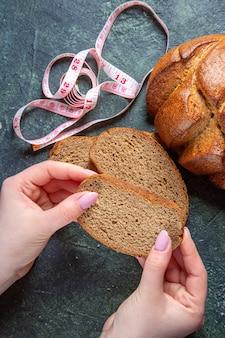 暗い机の上に女性の手で上面図暗いパンのパン