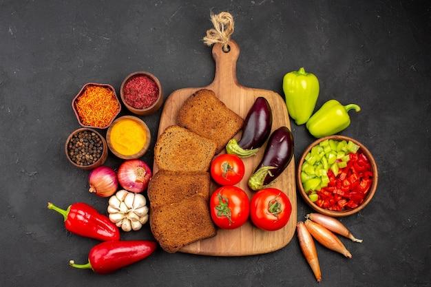 Vista dall'alto pagnotte di pane scuro con verdure fresche su fondo scuro piatto salutare per insalata