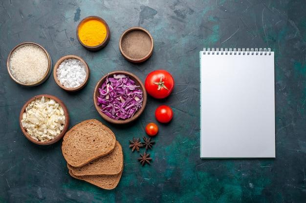 ダークブルーの机に調味料とスライスしたキャベツを添えたトップビューのダークパンのパン野菜料理食事皿パンの色