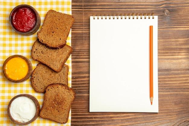茶色の木製テーブルパンのスパイシーな調味料に調味料を入れた上面図の暗いパンのパン