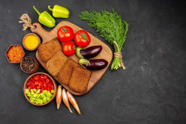 Top view dark bread loafs with seasonings tomatoes and eggplants on dark background salad health ripe meal