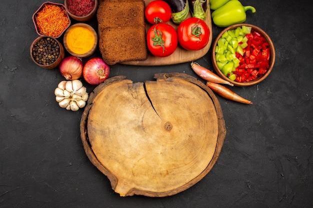 Vista dall'alto pagnotte di pane scuro con condimenti e verdure su fondo scuro piatto salutare per insalata