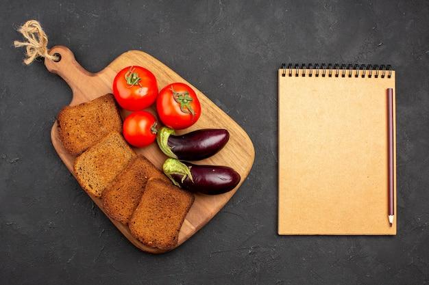 暗い背景にトマトとナスのトップビューの暗いパンのパンサラダ健康熟した食事
