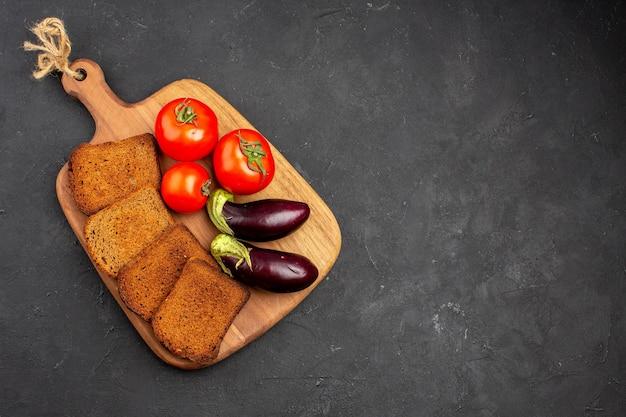 Vista dall'alto pagnotte di pane scuro con pomodori e melanzane sul pasto maturo per la salute dell'insalata di sfondo scuro