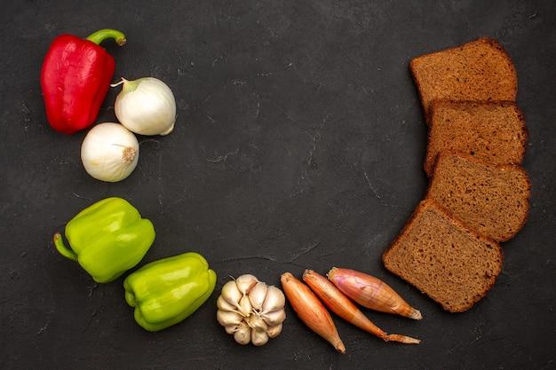 暗い空間に野菜とトップビューの暗いパンのパン