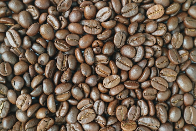 Top view of dark brown aromatic roasted coffee beans for background