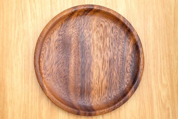 Top view of dark brown wooden plate on light wood counter