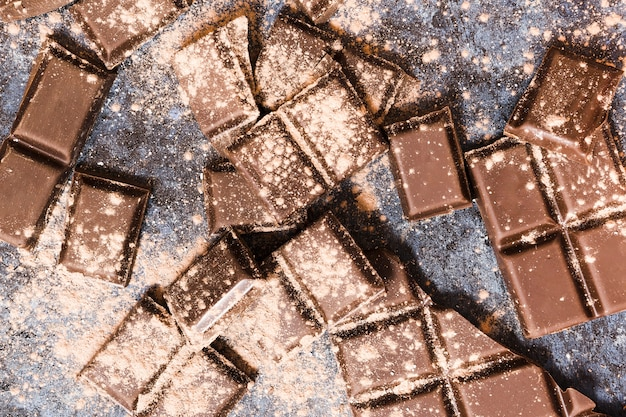 Top view dark chocolate tablets covered in cocoa