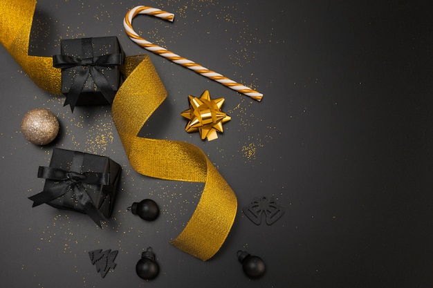 Top view of dark christmas presents with golden ribbon