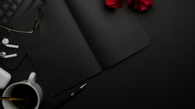 Top view of dark concept workspace with notebook keyboard stationery cup and roses on the table