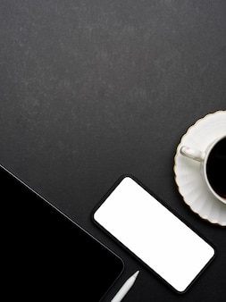 Top view of dark creative flat lay workspace with smartphone, tablet, coffee cup and copy space, clipping path
