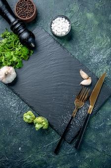 Вид сверху темная разделочная доска с приправами, столовыми приборами и зеленью на синей поверхности, цветная вилка, спелый салат