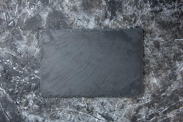 Scrivania scura vista dall'alto su una superficie grigio chiaro